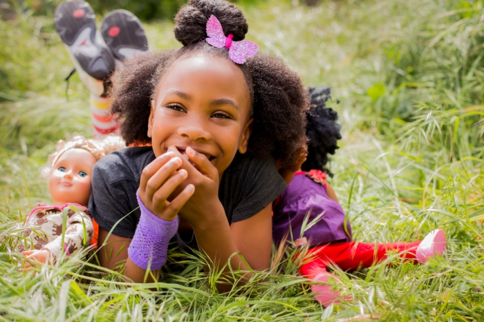 Black girl playing with dolls in tall grass